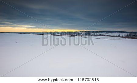 Winter Field Landscape Under Cloudy Sky.