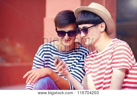 Young Male Couple Chatting On Mobile Device