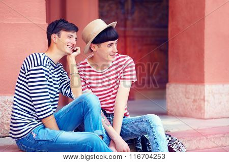Happy Young Male Couple Sitting On Stairs