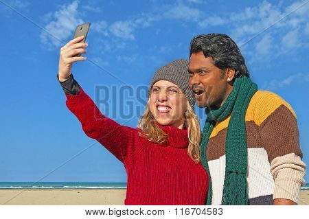 interracial couple of friends take selfie photo with smartphone