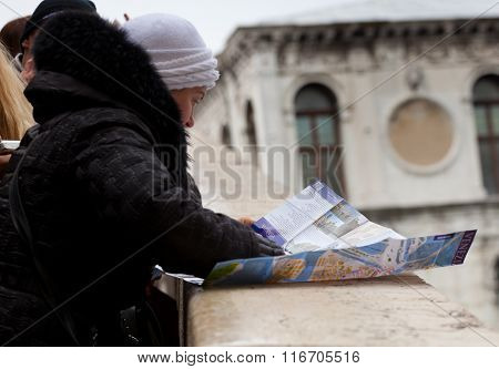 A Tourist Looks The Map Of Venice