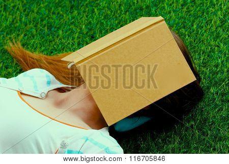 Beautiful young woman lying on green grass .