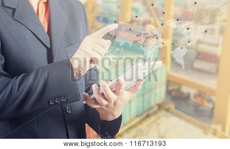 Businessman hand working and smart phone and laptop on Industrial Container Cargo freight ship background (Elements of this image furnished by NASA)