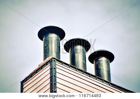 Black chimneys against the blue sky