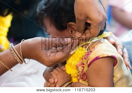 Baby girl crying in the karnavedha events. Traditional Indian Hindus ear piercing ceremony. India special rituals for children.