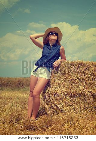 Woman with hat resting on a bale of straw on the field
