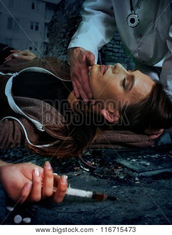 Portrait of  woman addicted to syringe on  brick wall background.
