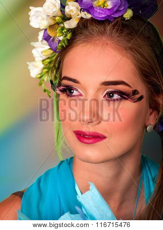 Woman with false eyelashes  and flowers in hair easter style .