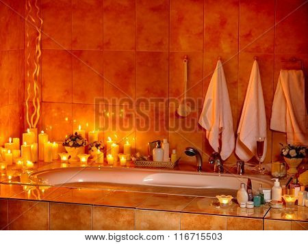 Home bathroom interior with bubble bath and burning candle.