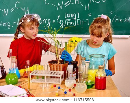 Children holding flask and plant in biology chemistry class.