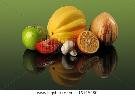 Fresh fruits and vegetables on reflective table over green background