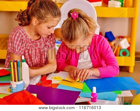Two girls friend  kids gossip and craft colored paper on table in kindergarten .