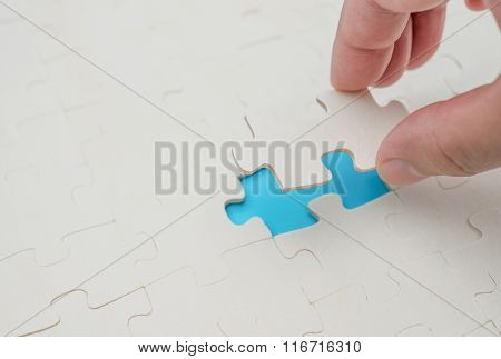 Finishing The Last Piece Of A Jigsaw Puzzle Game On Blue