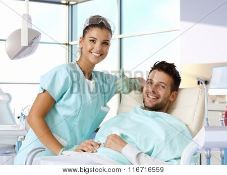 Portrait of attractive female dentist showing thumb-up sign, while patient smiling in dentist's chair.