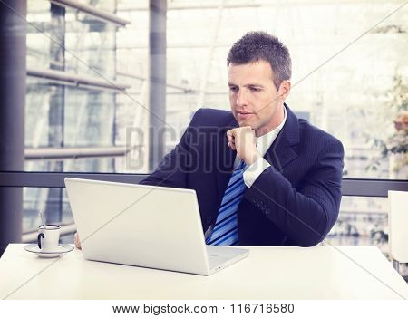 Busy businessman in suit working with laptop at office desk, concentrating, thinking.