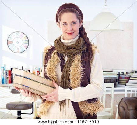 Portrait of happy smiling schoolgirl holding books, looking at camera.