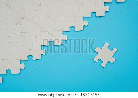 Jigsaw Puzzle With One Piece Separated On A Blue Background