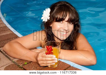 Young attractive woman in the pool and coctail in he hand