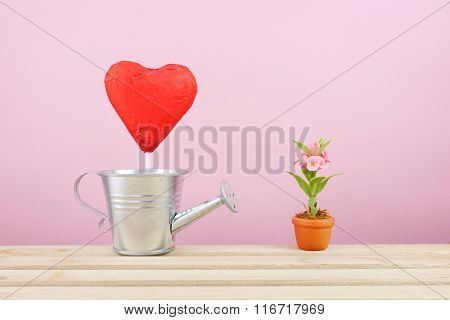 The red foiled chocolate heart stick with small silver watering can