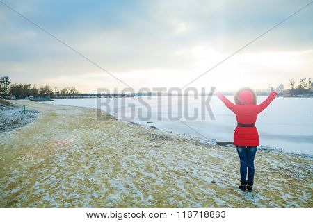 a girl stands near the edge of the river in winter with heaved up hands top