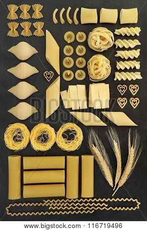 Large dried pasta food selection with natural wheat ears forming an abstract background on grey slate.
