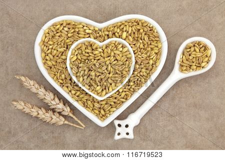 Kamut khorasan wheat grain health food in heart shaped porcelain dishes and spoon with sheaths over brown grunge paper background.