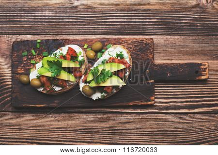 Tasty snack of open sandwich with avocado and soft cheese on wooden cutting board. Top view