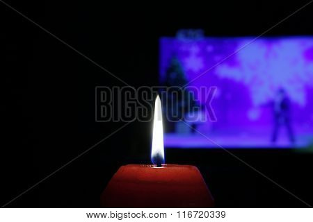 The red flame of the red candle in the dark