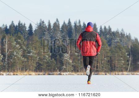 Sportsman taking part in trail running race outdoor in winter
