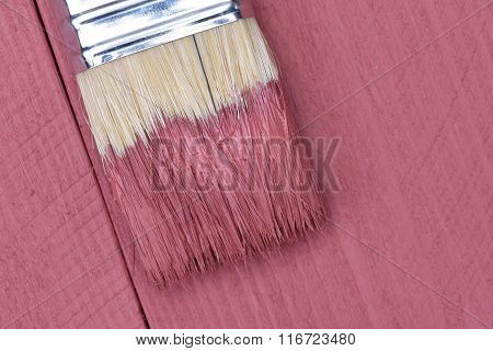 Pink paint brush on wooden background