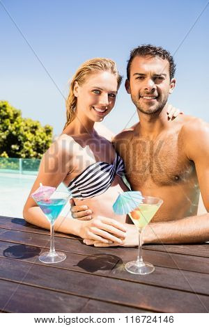 Happy couple embracing in the pool with cocktails on the pool edge