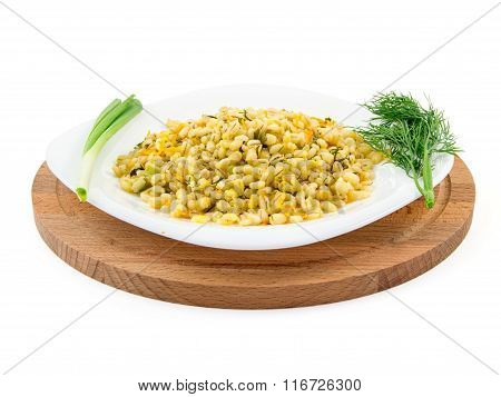 Barley porridge in a plate with vegetables, dill and green onion, selective focus.