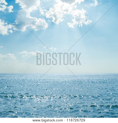 blue sea with reflections under clouds and sunshine