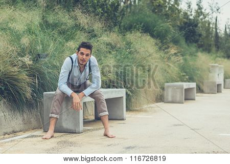Young Handsome Man Sitting On A Concrete Bench
