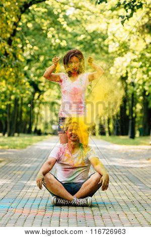 Young And Beautiful, Hipster Couple Playing In The Park On Holi Color Festival With Colour Paint Pow