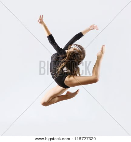 Young girl engaged art gymnastic on grey