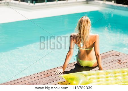 Rear view of peaceful blonde sitting on pools edge
