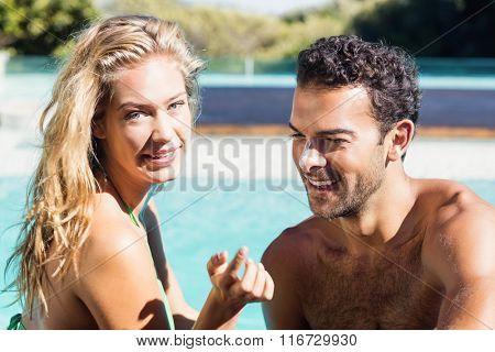 Girlfriend applying cream to boyfriend at the pool
