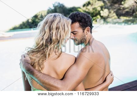 Rear view of couple sitting by the pool nose to nose