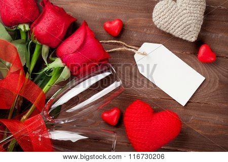 Valentines day red roses and champagne over wooden background