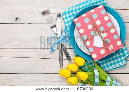 Easter with yellow tulips and gift box. Top view with copy space