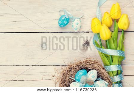 Easter background with blue and white eggs in nest and yellow tulips. Top view with copy space. Vintage toned