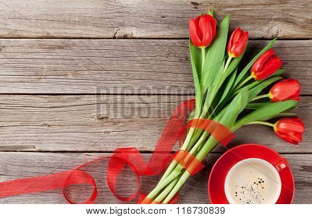 Red tulips and coffee cup on wooden table. Valentines day background. Top view with copy space