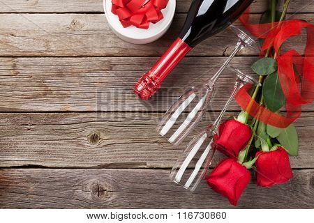Red roses with Valentines day gift and champagne over wooden background. Top view with copy space