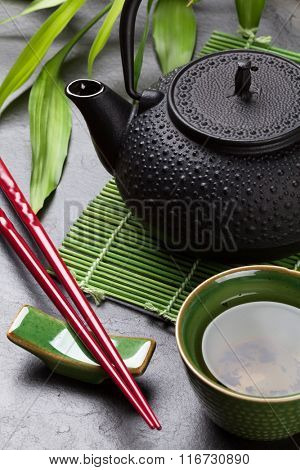 Asian tea bowl and teapot over stone table