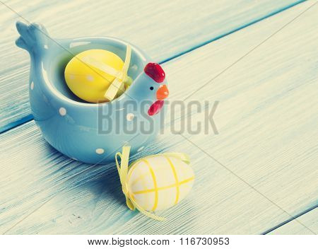 Easter eggs and decor on blue wooden table. View with copy space. Vintage toned