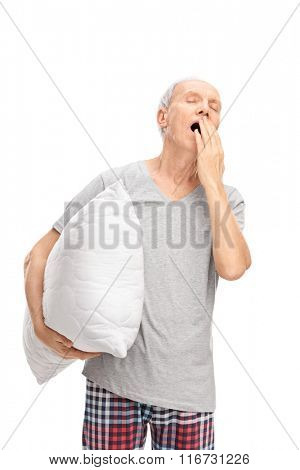 Vertical shot of a sleepy senior man holding a white pillow and yawning isolated on white background
