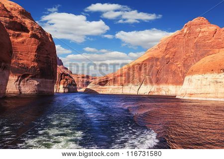 The lake Powell on  river Colorado. The foamy trace from powerboat crosses emerald waters. Hills from red sandstone surround the lake