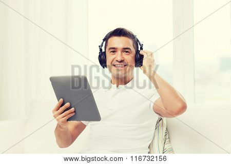 smiling man with tablet pc and headphones at home