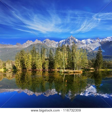 Dreamlike beauty lake and park. In smooth water reflected snow-capped mountains surrounding the mountain resort of Chamonix
